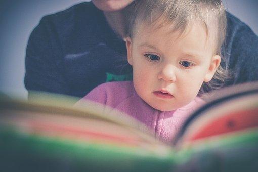 親に絵本を読み聞かせしてもらう子供