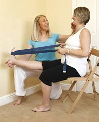 椅子に座ってゴムチューブを使い介護予防運動をしている
