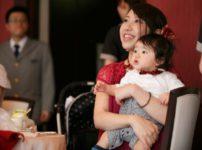 赤ちゃんと結婚式に出席する母親