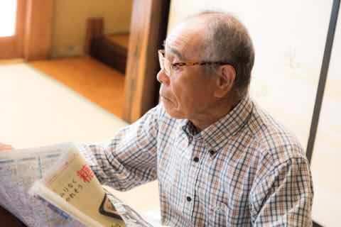 居間で新聞を読む老紳士