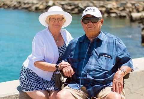 波止場で手を取り合い座る高齢者夫婦