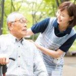 公園のベンチに座る老紳士に声をかける女性