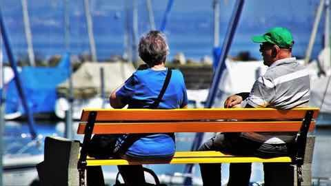港でベンチに座っているシニア世代のカップル