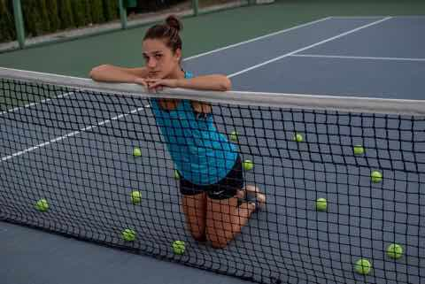 テニスのネットにもたれかかる少女
