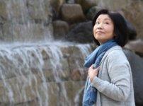 滝のまえで振り返るシニア女性