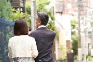 腕を組んで街を歩くシニア世代のカップル