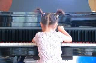 ピアノを弾く女児の後ろ姿
