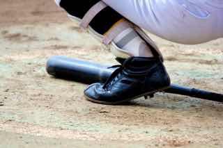 金属バットと球児の足