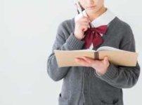 ノートを開いて考え事をしている女子高生