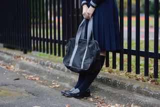 バッグを持ち鉄柵にもたれているセーラー服の女子生徒