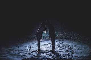 夜の雪の中でライトアップされる男女