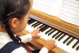 ピアノのレッスンを受ける女児の後ろ姿