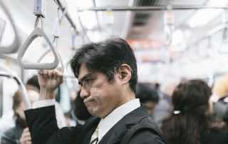 電車で渋い顔をして立っているサラリーマン