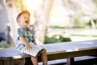 本を開いて大笑いしている子供