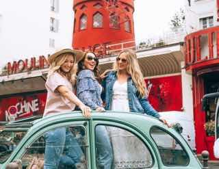 車の天井から街の外を眺める女子3人