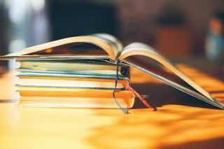 日なたのテーブルに積み上げられた本