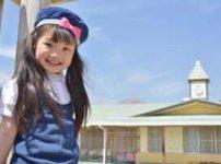 幼稚園前でニコニコ笑顔の女児