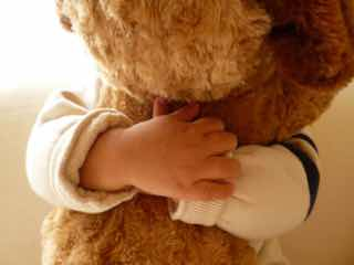 小さな子に抱きしめられる大きなぬいぐるみ
