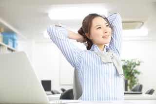 オフィスで背伸びをする女性