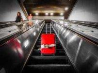 エスカレーターを登る赤いキャリーバッグ