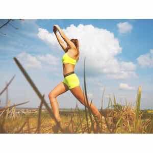 野原でエアロビクスする女性