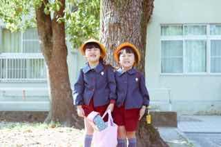 木の前で並んで写真を撮ってもらう男児二人