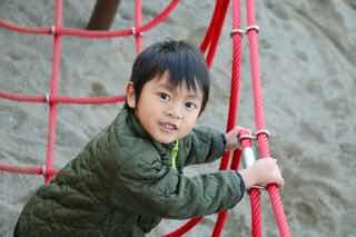 アスレチックで遊ぶ男児