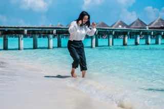 リゾートのビーチで裸足で海に入る女性