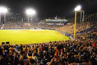 野球場で大勢の観客が盛り上がっている