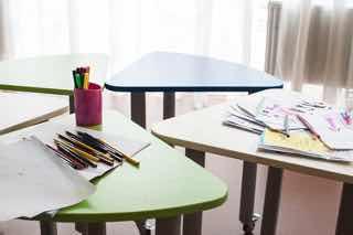 雑に並べられた机と筆記用具