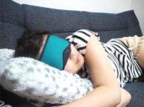 アイマスクをつけてソファで寝る女性