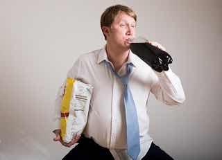 スナック片手にコーラを飲む男性