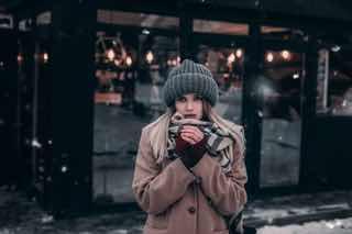 冬の街で寒そうに外で待っている女の子