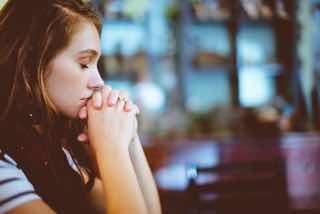 両手を組み合わせて祈る女性