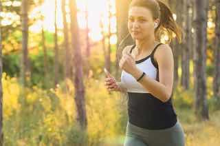 林でジョギングする女性