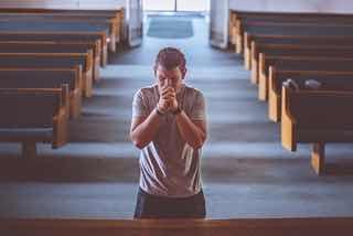 手を組んで教会で祈る男性