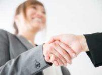 笑顔で握手するスーツの女性