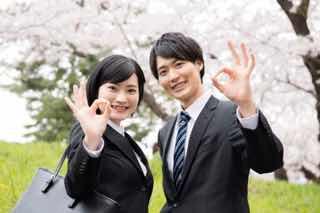 桜をバックにポーズする新社会人の男女