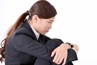 膝を抱えて悩むスーツ女性