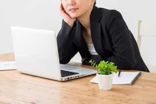 パソコンを前に頬杖をつく女性