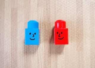 笑顔が書かれた赤と青のキャップ