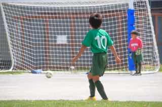 サッカーでシュート練習する少年