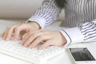 スマホを置いてパソコン操作する女性