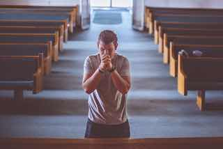 教会で祈る男性