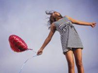ハートの風船を持ってジャンプする少女