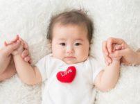 両親に両手を握られる赤ちゃん