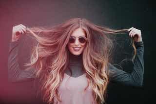 髪を両手で伸ばす女性