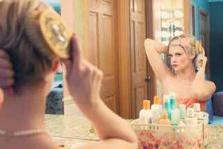 鏡を見てメイクする女性