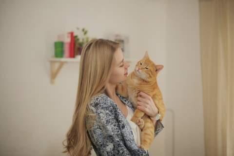 だっこした猫に話しかける女性