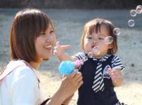女児とシャボン玉で遊ぶ保母さん